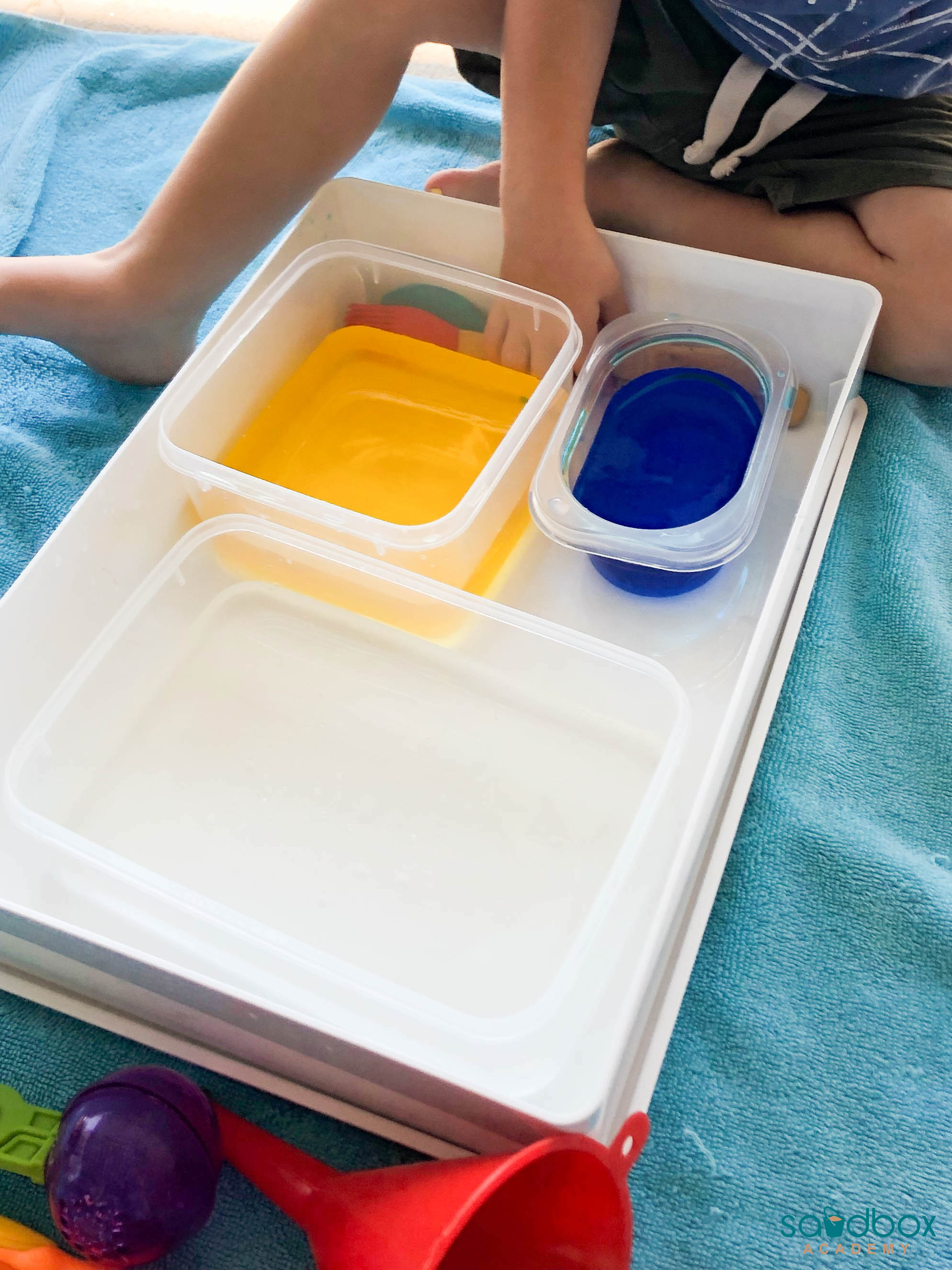 blue and yellow water in a larger bin for sensory play