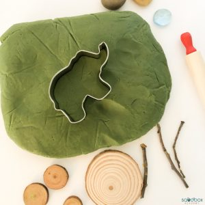elephant cookie cutter on green play dough surrounded by small wood discs, sticks, rocks, and a rolling pin.