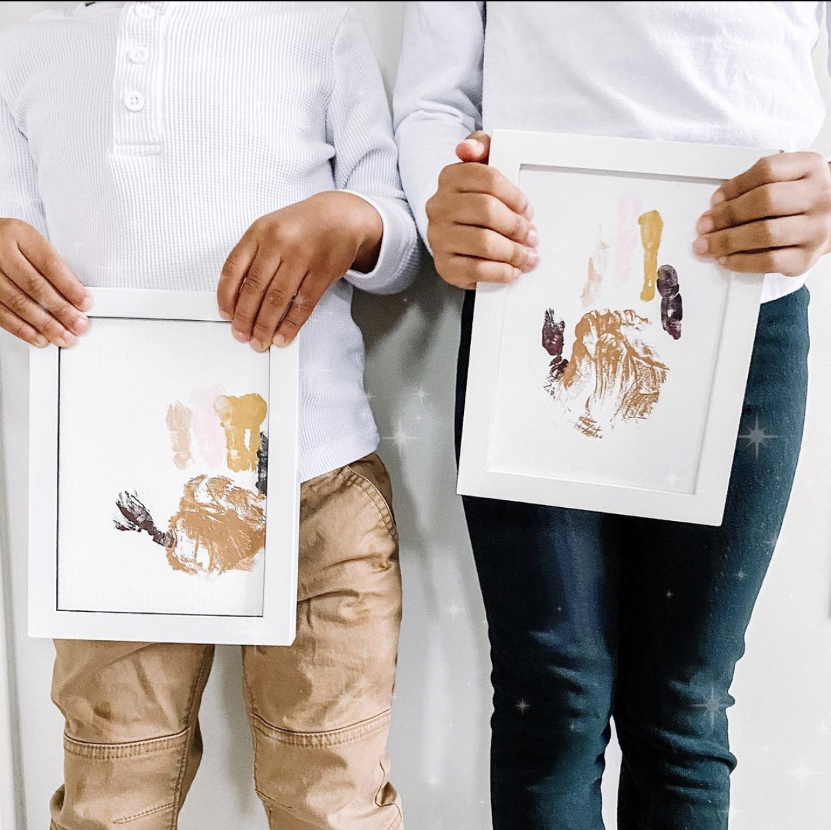 two kids holding framed artwork. Artwork is their handprint in various shades of brown