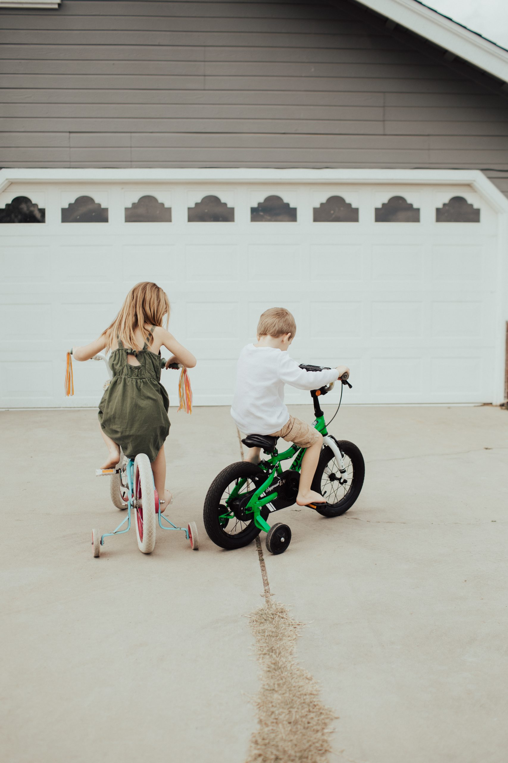 every kid needs play two kids riding bikes in the driveway