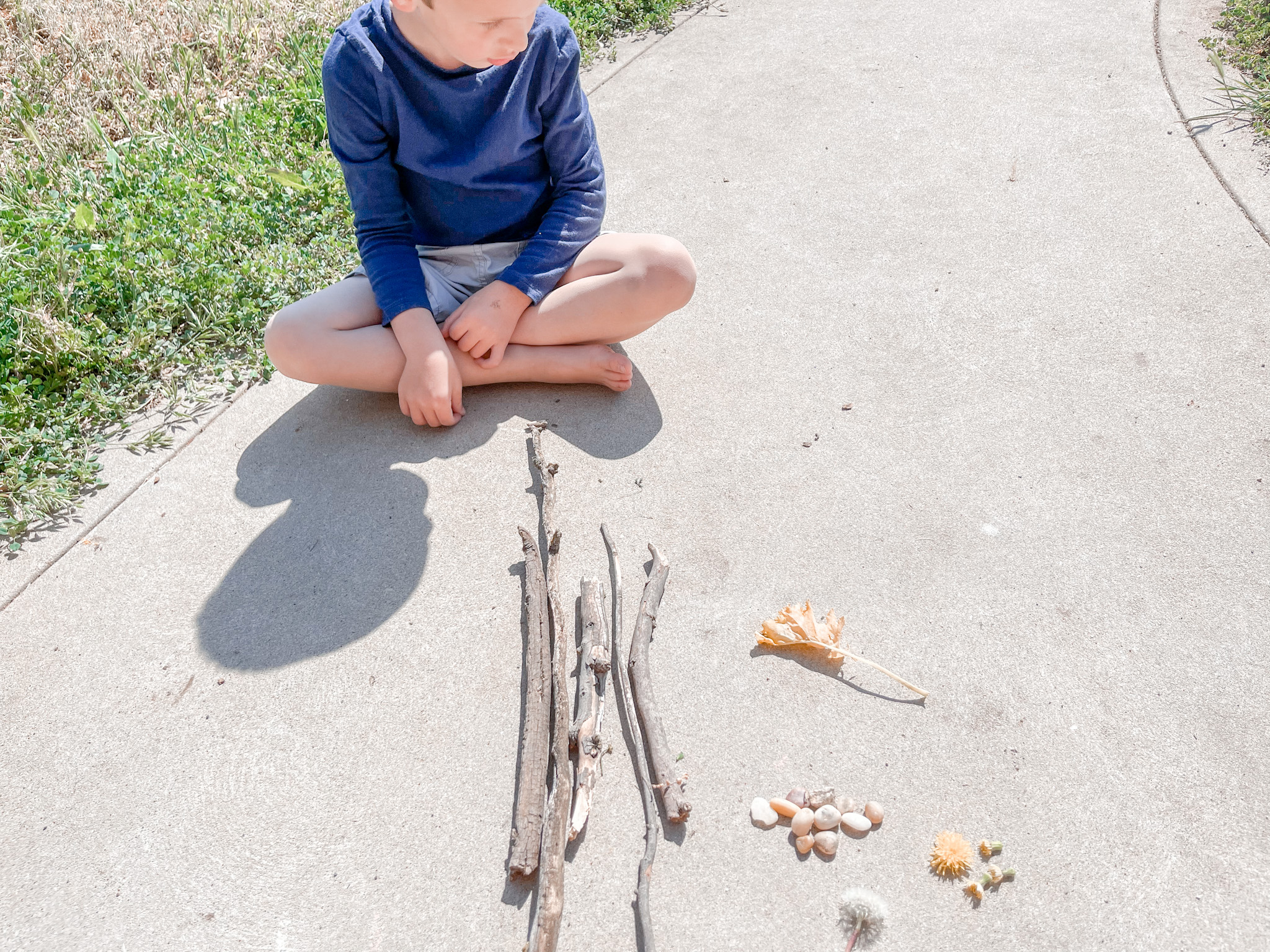 little boy outside sorting nature to practice math skills outside