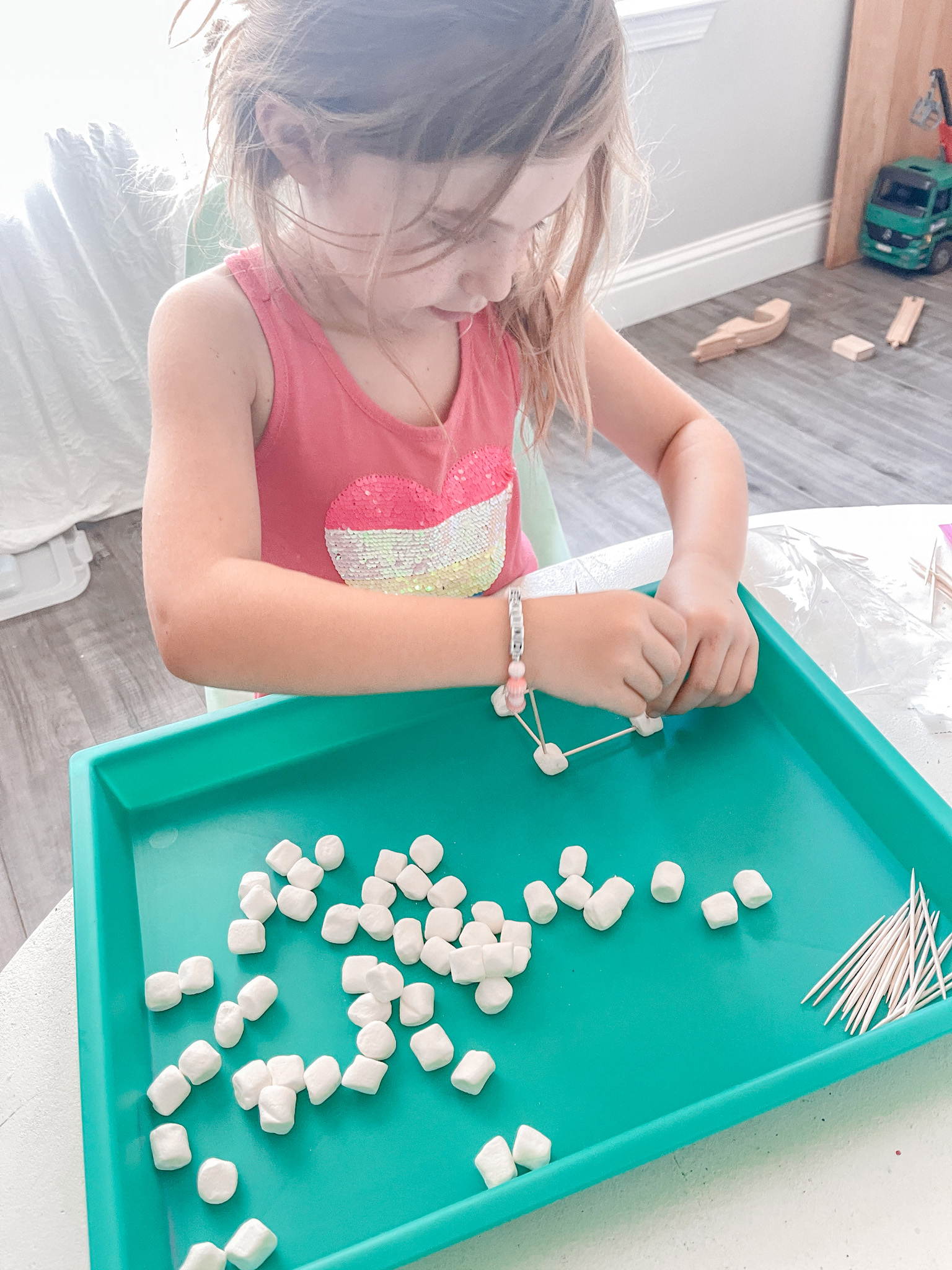 little girl building with marshmallows and toothpicks for a summer stem activity